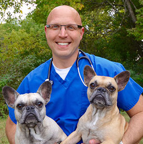 Dr. Brett Wasik with two pugs