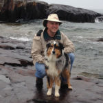 Dr. Kevin Stepaniuk with a dog on the shore
