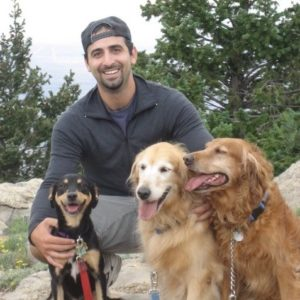 Dr. Zachary Wright with three dogs in the mountains